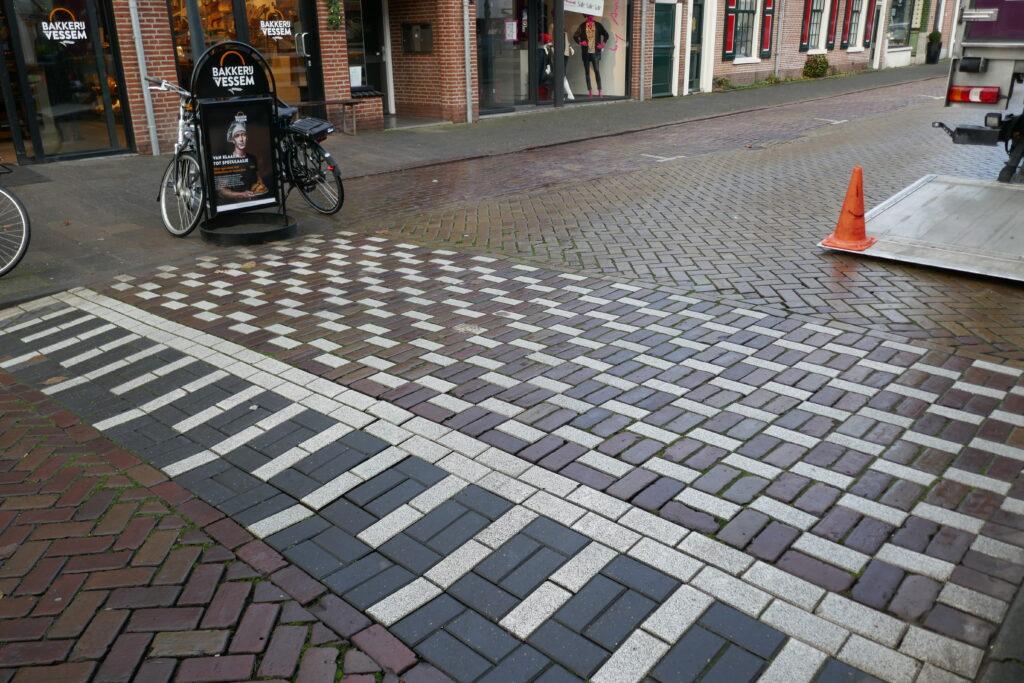 Het blokjes patroon (zebramat) op de Raadhuisstraat wat als oversteekplaats zou moeten dienen